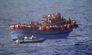 Picture from the Guardian website: A motor boat from the Italian frigate Grecale approaches a boat overcrowded with migrants in the Mediterranean. Photograph: Italian Navy/AP